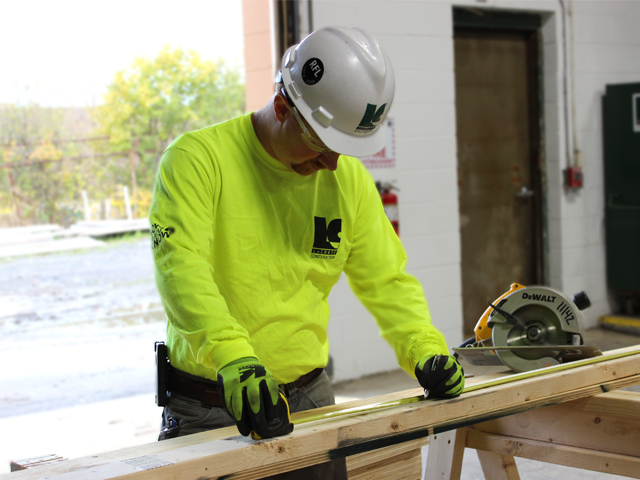 Construction worker measuring a piece of wood.