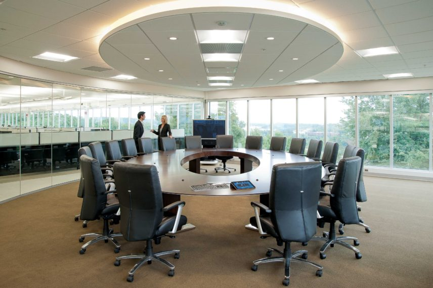Large corporate meeting room with round table and chairs with two associates having conversation.