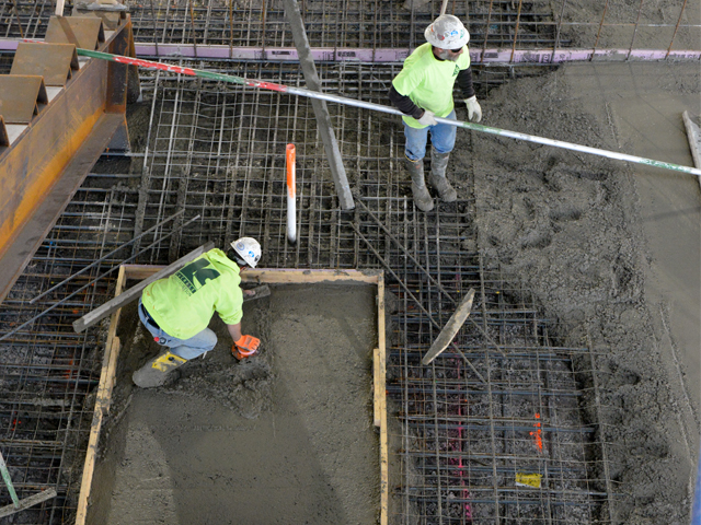 Two construction workers standing in rebar working on concrete.