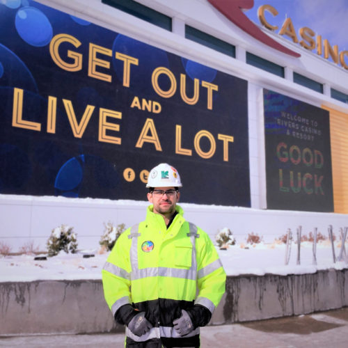 Young male construction worker in front of casino LED screen that says 'Get out and live a lot.'