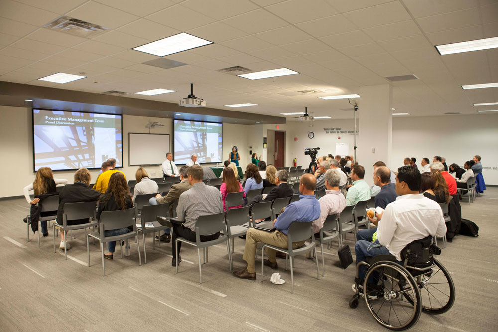 Training room with a large group, interacting in a panel discussion.