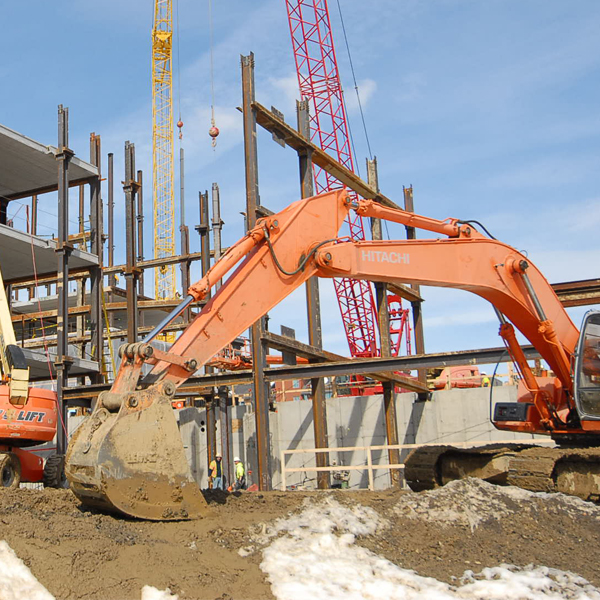 Construction site with excavator in foreground and erected steel in the background.