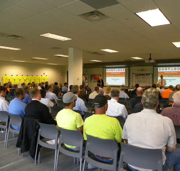 Large meeting room, with people sitting and listening to a safety presentation.