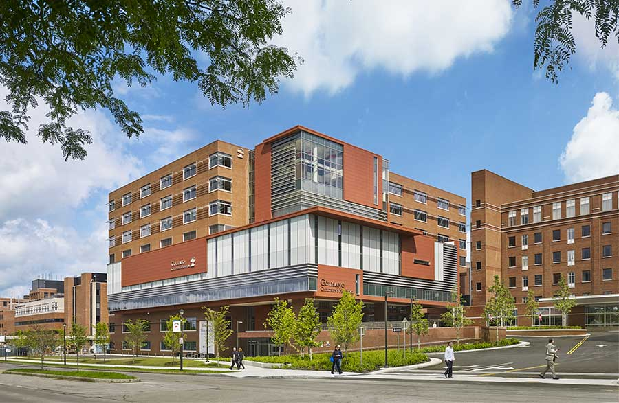 Modern large brick hospital with glass windows.