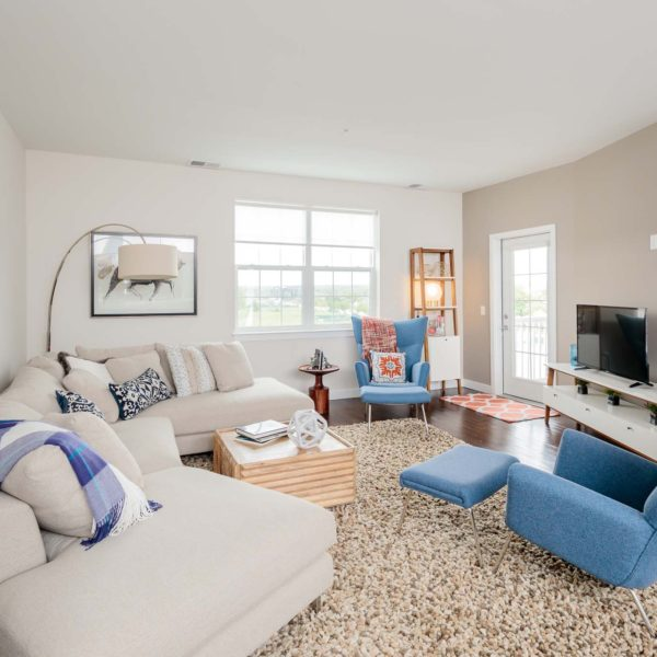 Family room with a white couch, blue chairs and a t.v.