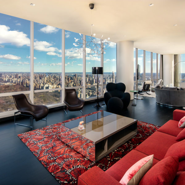 Large red couch, chairs and furnishings over looking the city skyline