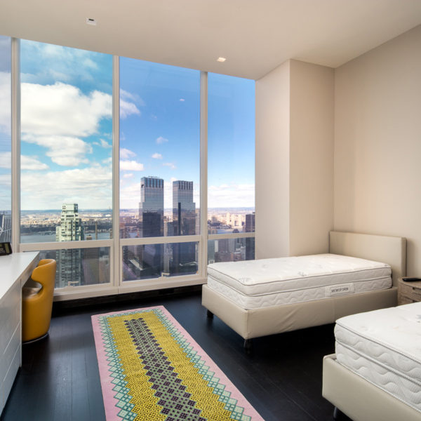 Bedroom with two beds overlooking city skyline