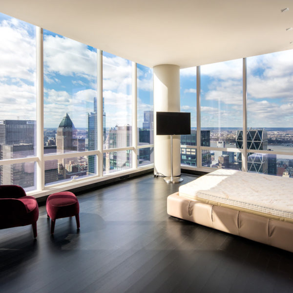 Penthouse bedroom with chair and bed overlooking city skyline.