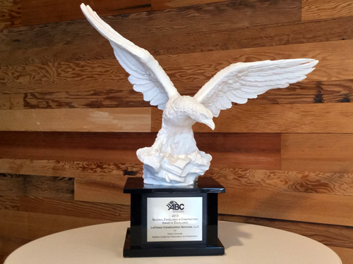 Award that is a statue of an eagle on a white table against wood background.