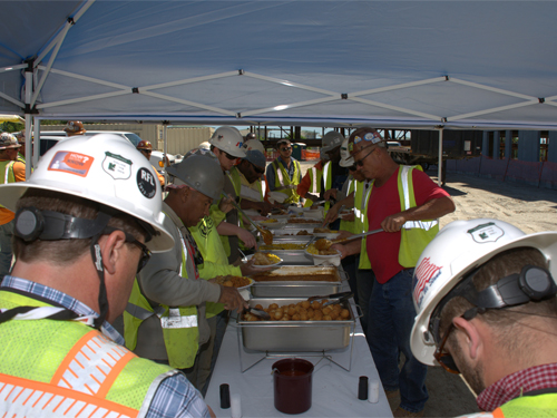 Two lines of construction workers on either side of a lunch buffet under a tent on a project site.