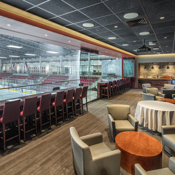 VIP box with a row of seats at the glass and tables and chairs for lounging