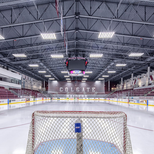View from behind the hockey net facing the other end of rink with open seats on either side
