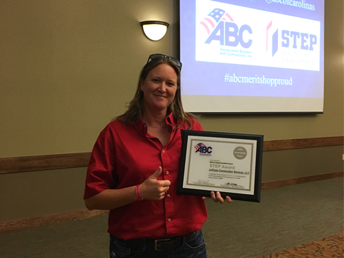 Woman holding an award plaque in front of a projector screen with ABC and STEP logo.