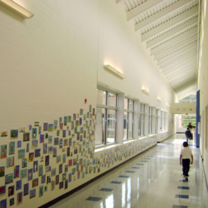 Hallway with photos on the wall and child walking in the hall.