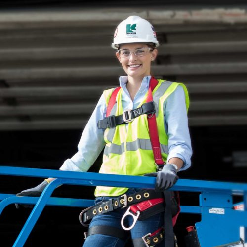 Young female construction worker in a scissor lift.