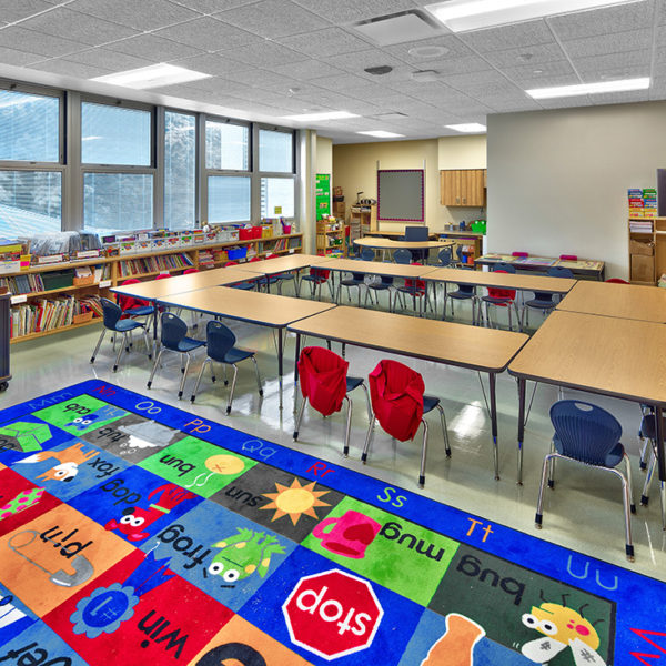 Elementary classroom with bright colored carpet and furniture