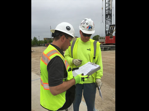 Two construction workers reviewing project tasks on a clipboard.