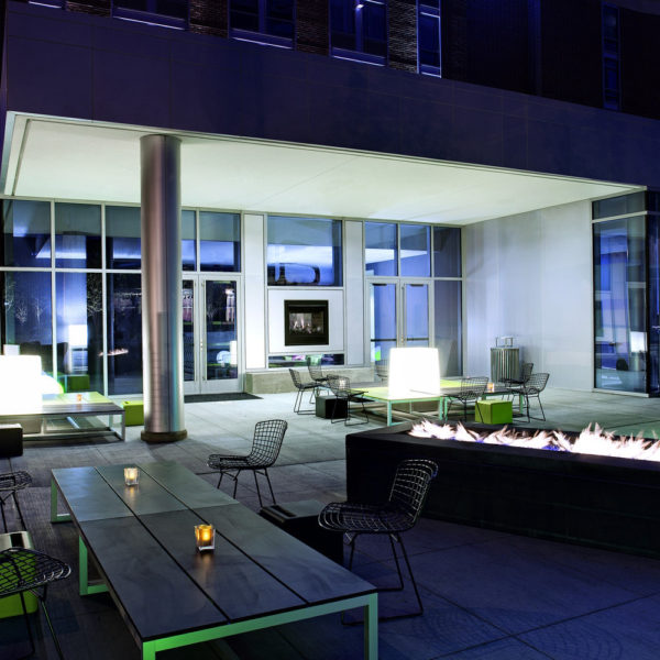 Outdoor patio at night with tables, chairs and fire pit