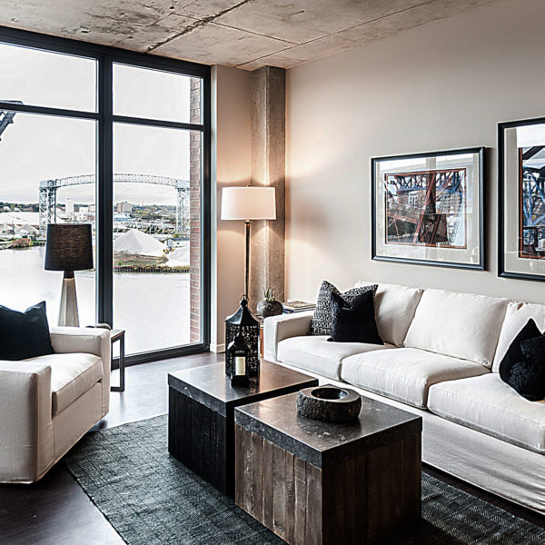Apartment living room with couches and coffee table overlooking river.