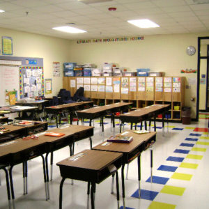 Classroom with desks, white board and cubbies