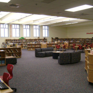 Library with book shelves along the walls and couches in the middle