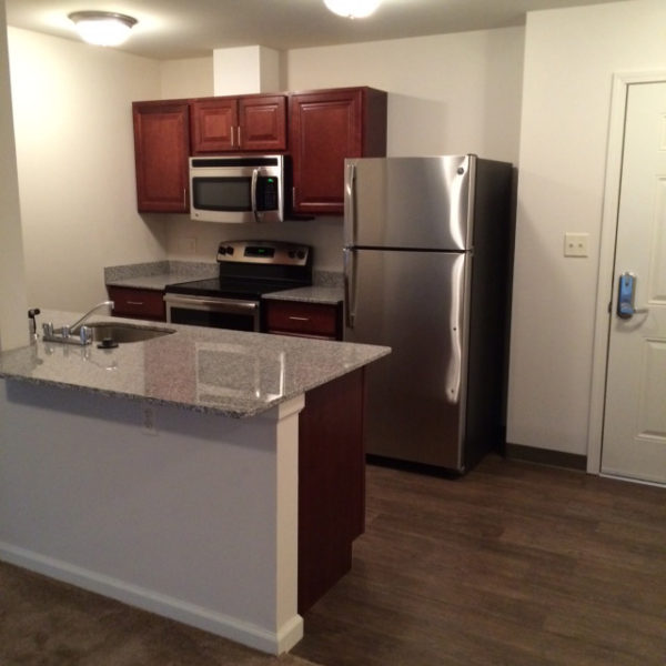 Apartment kitchen with stainless steel appliances and cabinets