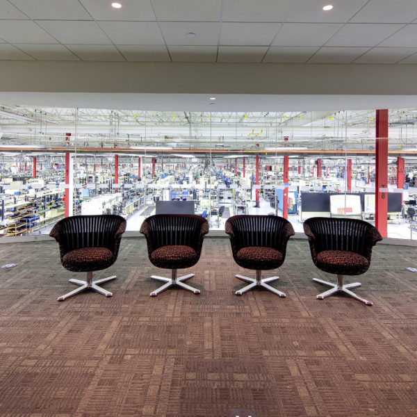 Four chairs overlooking glass wall into manufacturing space