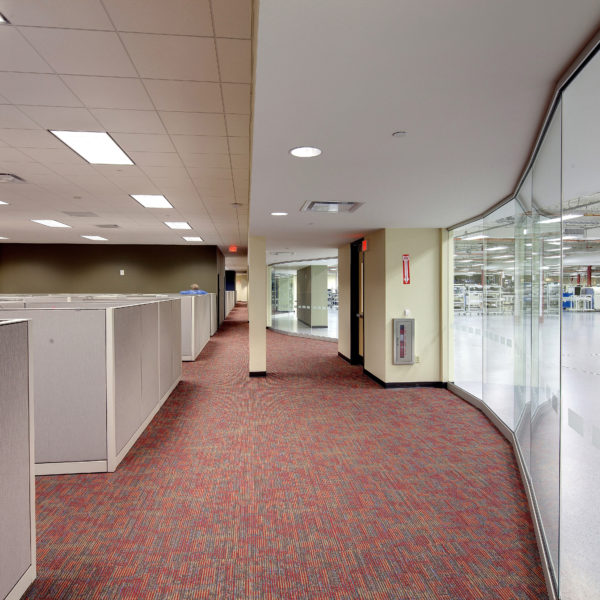 Office hallway with cubicles to the left and glass wall looking into manufacturing space to the right
