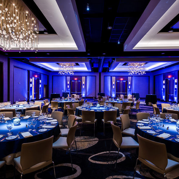 Banquet room with tables and chairs with blue back lit lighting.