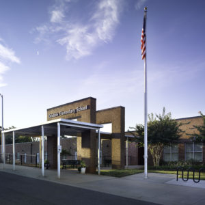 Exterior of school with American flag and blue sky.