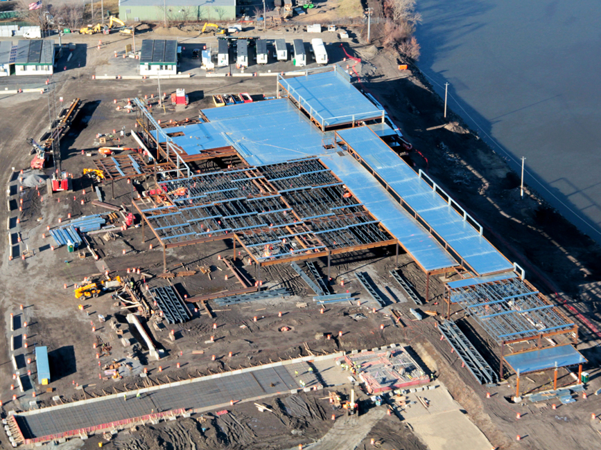Aerial shot of steel and partially constructed building on a project site adjacent to a river.