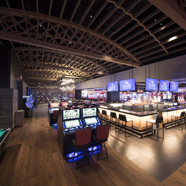 Casino bar with tv screens, gaming machines and exposed wooden tresses.