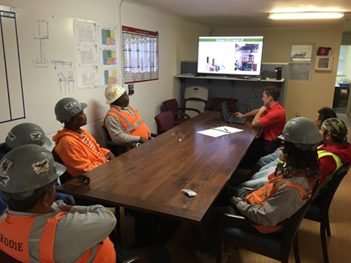 Group of construction workers sitting at a table in construction trailer, watching a training video.