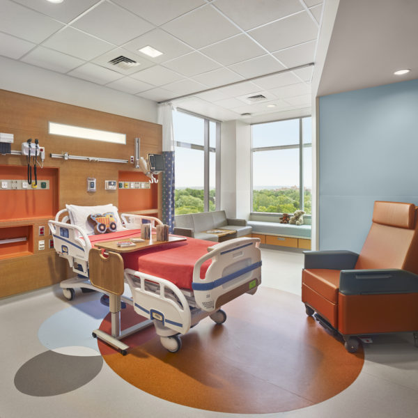 Colorful paitnet room with hospital bed and chair.