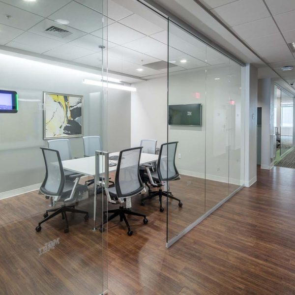 Glass walled conference room with table and chairs