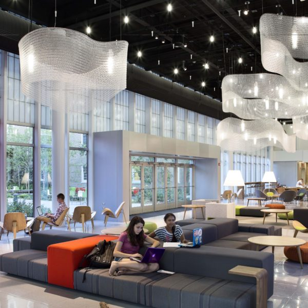 Lobby space with unique lighting and lounge furniture with students