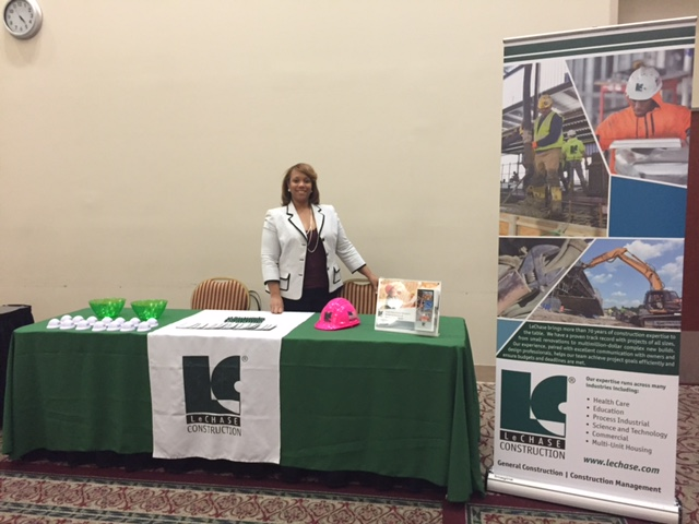 Women standing behind LeChase table with pull up banner at a conference.