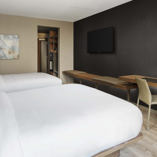 Hotel room interior with two standard beds, couch, desk and furnishings