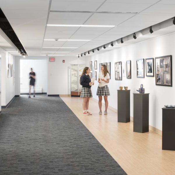 Gallery space with artwork to the right and students