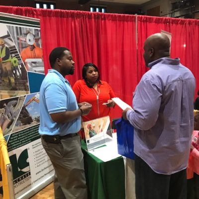 Three people standing a trade show booth talking.