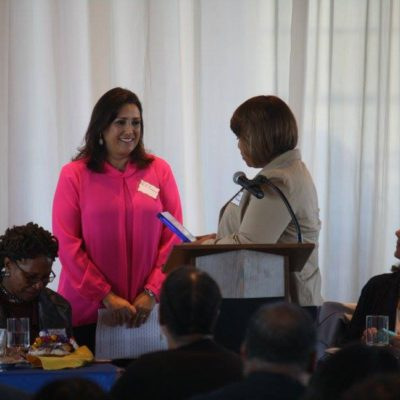Woman at podium presenting an award to another women.