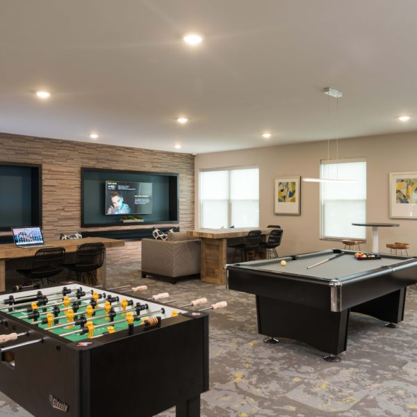 Gaming room with billiards and Foosball tables and large wall mounted tvs and lounge furniture.