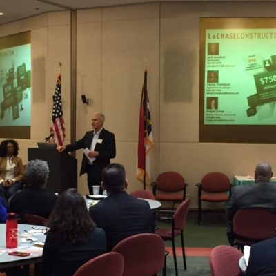 Man presenting to a small group of people at NC State Industry Day.