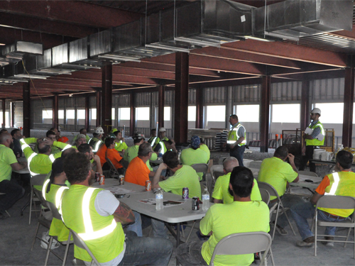 Men site a tables under steel frame of building.