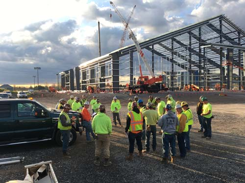 Workers stand in circle having discussion on project site.