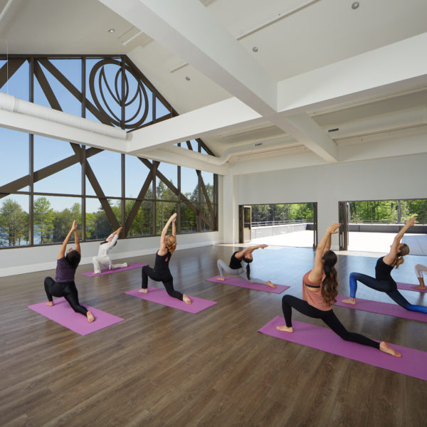 Grand yoga hall with people on yoga mats
